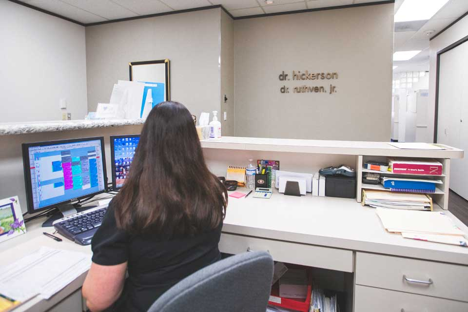 A receptionist viewing dental appointments of patients at Hickerson & Associates, DDS. PC..